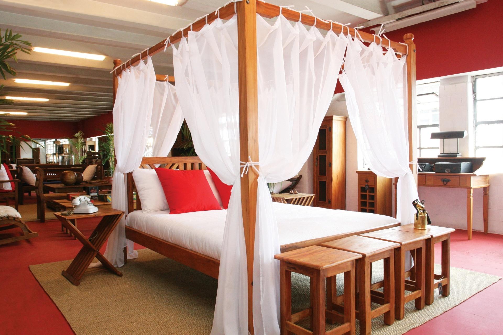 A cama com dossel em peroba rosa de demolição tem cortinas de voal branco. O projeto é de Jorge Garcia, proprietário da loja Trapiche Carioca