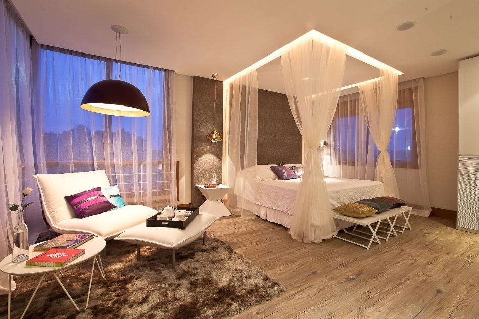 Em vez da tradicional armação, os véus que envolvem esta cama partem do recorte feito no forro de gesso e do painel revestido com papel de parede que imita tecido. A iluminação embutida é feita com corda luminosa. O projeto é da arquiteta Caroline Froeder Seferin