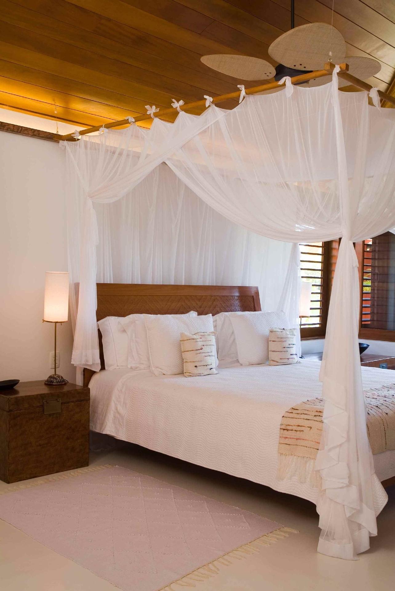 Na casa de veraneio projetada pelo arquiteto David Bastos, a cama com dossel integra o quarto do casal. Feito de cumaru, o dossel é recoberto por tule, tecido leve cuja trama tem minúsculas abertura que deixam passar o ar, mantendo o leito