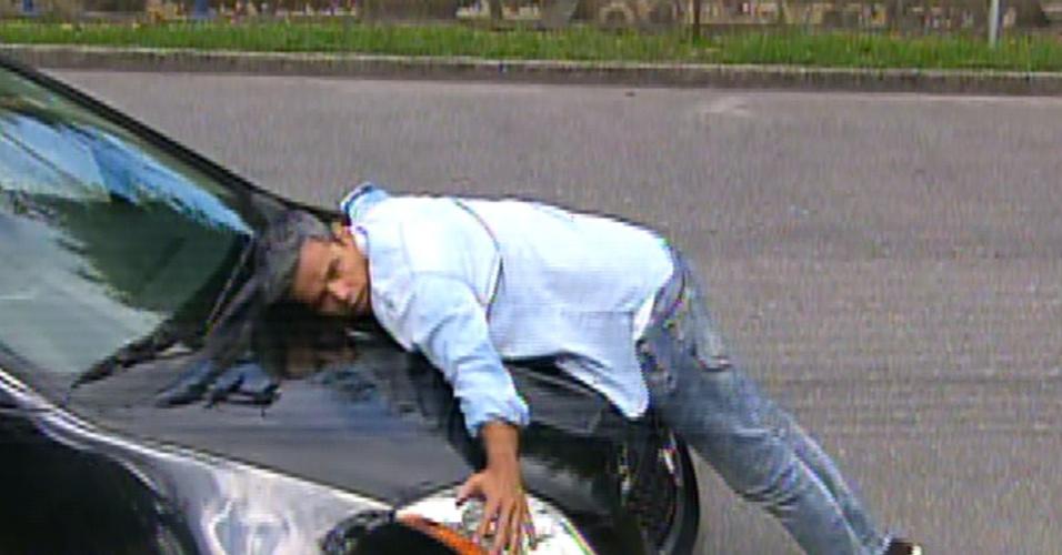 """31.jul.2013 - Em sua estreia no """"Video Show"""", Otaviano Costa se joga sobre carro para simular atropelamento"""
