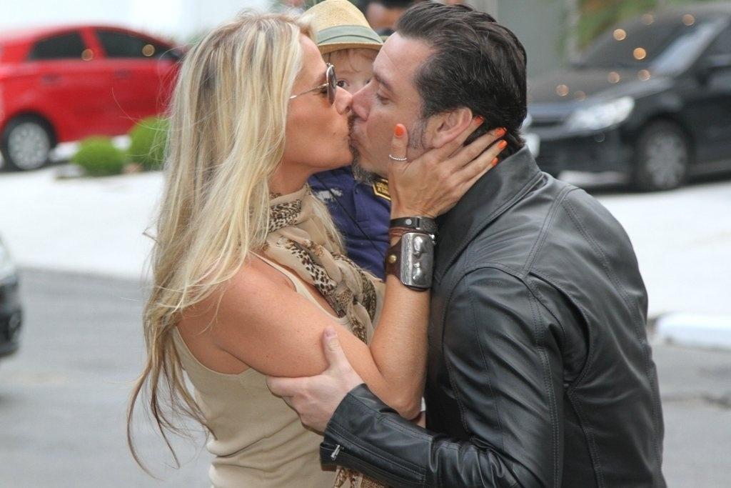 5.ago.2013 - Adriane Galisteu dá um beijo no marido, Alexandre Iódice ao chegar para a festa do filho Vittorio no buffet Planet Mundi, em Moema, São Paulo