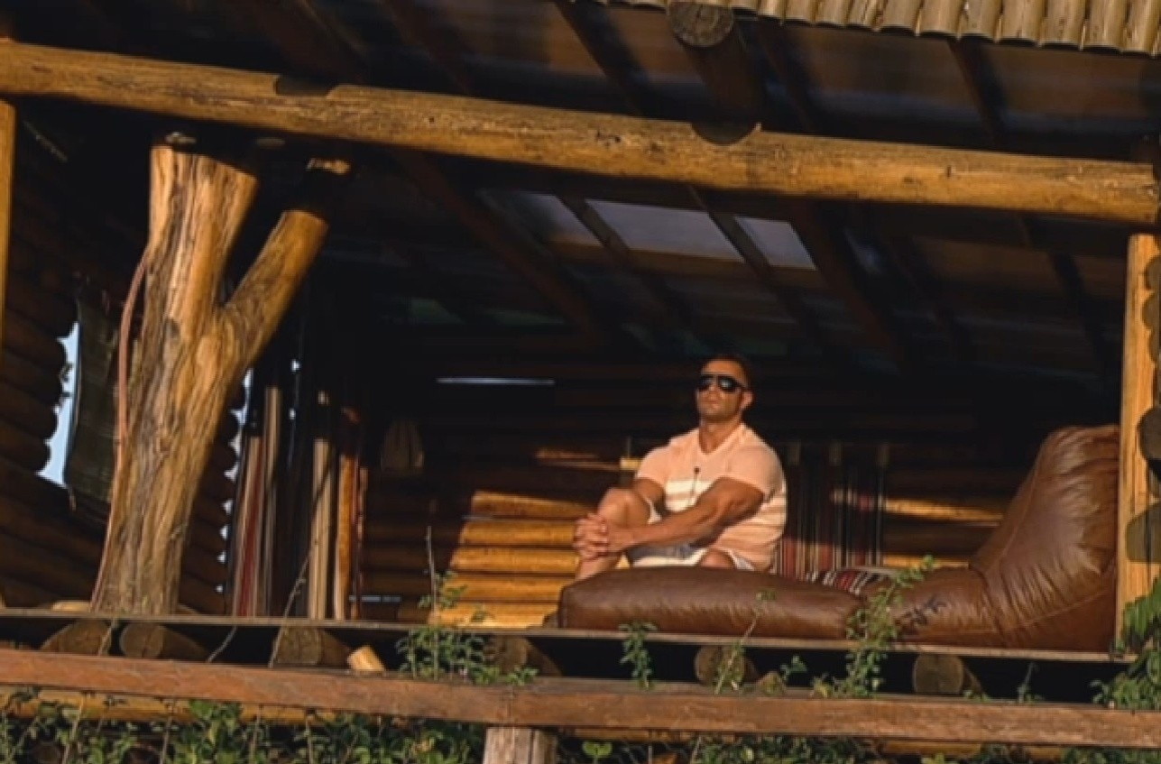 5.ago.2013 - Isolado, Marcos Oliver contempla o pôr do sol na casa da árvore