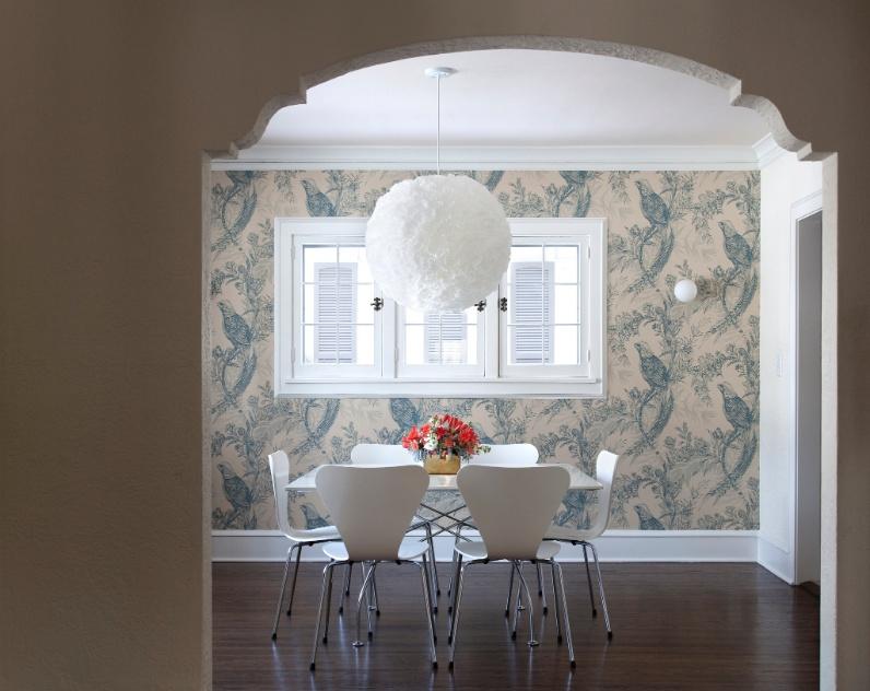 """(Imagem do NYT, usar apenas no respectivo material) Na sala de jantar o papel de parede """"toile"""", clássico, foi combinado a uma luminária feita de filtros de papel para coar café. A mistura do tradicional com o informal e o divertido reflete a influência da mãe e da avó da escritora Elizabeth Foy Larsen"""