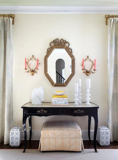 (Imagem do NYT, usar apenas no respectivo material) No hall, um aparador ganha evidência pela decoração simétrica: os castiçais de parede se repetem, assim como os objetos brancos dispostos nas laterais do móvel