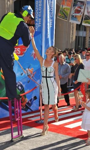 5.ago.2013 - Atriz Ashley Scott brinca com malabarista no tapete vermelho em Los Angeles