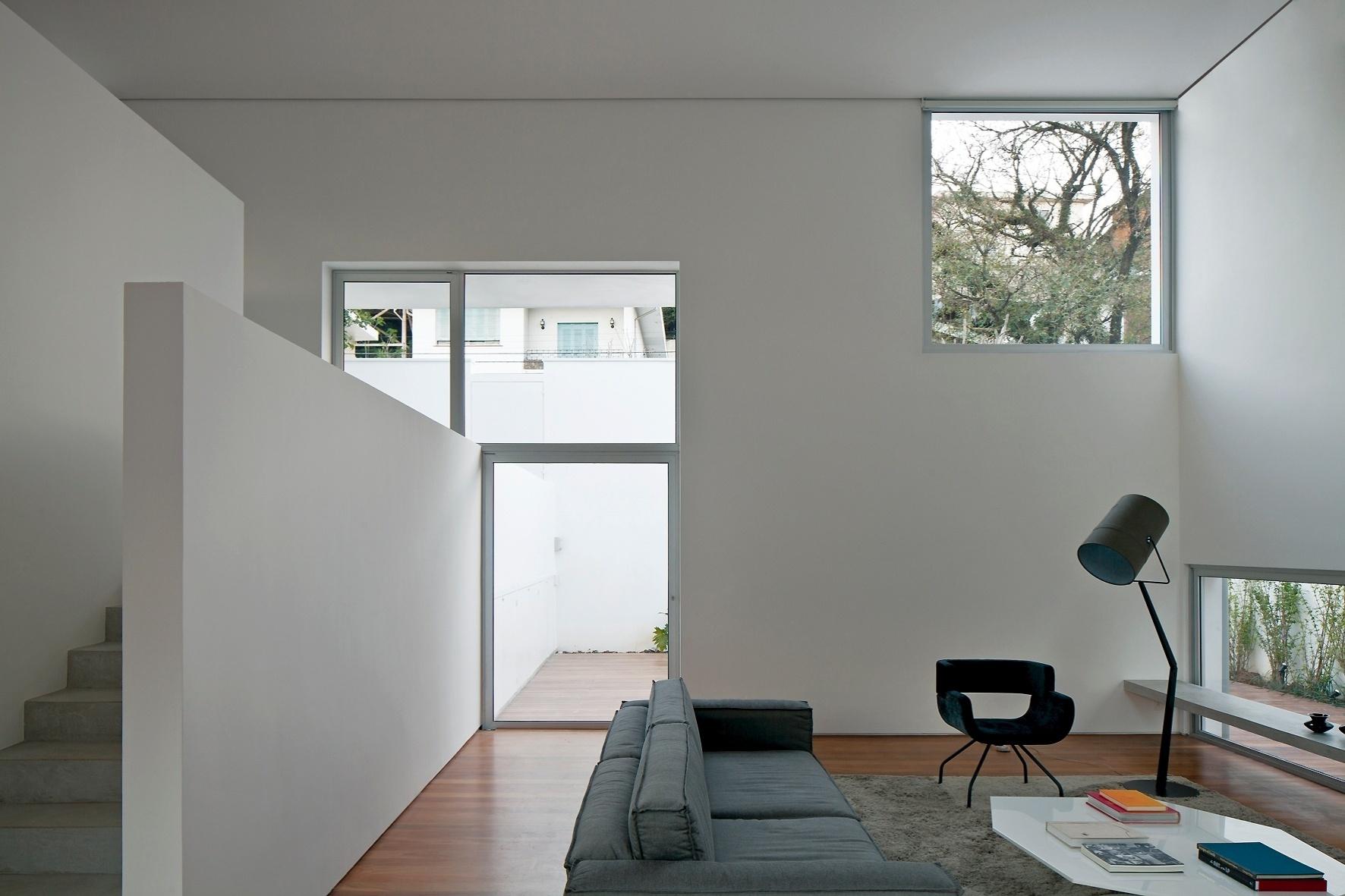 A sala de estar ganha reforço na iluminação natural por conta da janela no canto superior direito. O ambiente ainda tem saída direta para o pátio externo da residência reformada pelo escritório AR Arquitetos