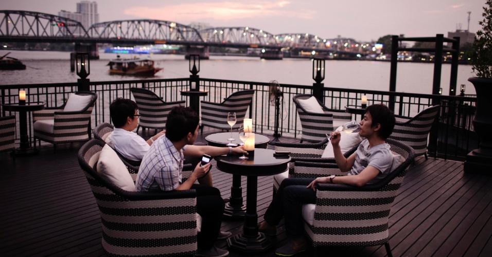 Hóspedes tomam vinho em terraço do Hotel Siam, em Bangcoc