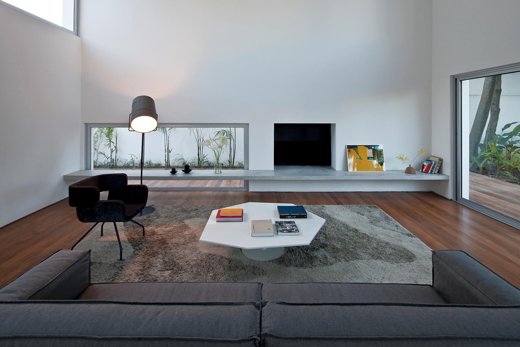 Na sala de estar - que ocupa o lugar da antiga garagem, no piso mais baixo da Casa dos Pátios - a decoração conta com móveis do Estúdio Bola e uma luminária de piso Fork, da Lumini. A abertura (à dir.) serve de espaço para lareira. O projeto arquitetônico é do escritório AR Arquitetos