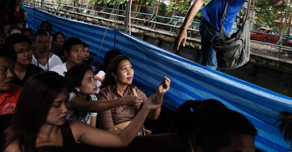Tailandeses usam barco para cruzar um dos canais de Bancoc