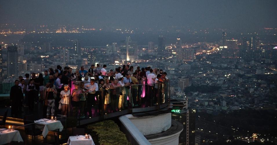 Visitantas observam a paisagem de Bangcoc a partir do Sky Bar Atop State Tower, uma das grandes atrações da capital tailandesa