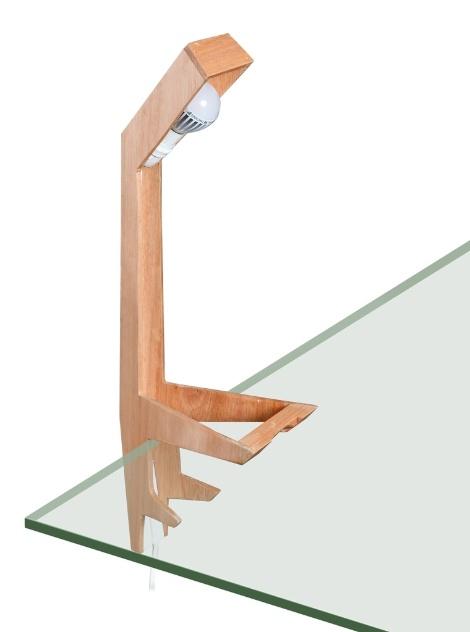 """Andrea Kac, Julia Castillo e Tatiana Lacrose, designers radicados em Montevideo, Uruguai, assinam a luminária de madeira Kaiju. A peça pode ser usada como luminária de mesa ou clipe, """"encaixada"""" à superfície"""