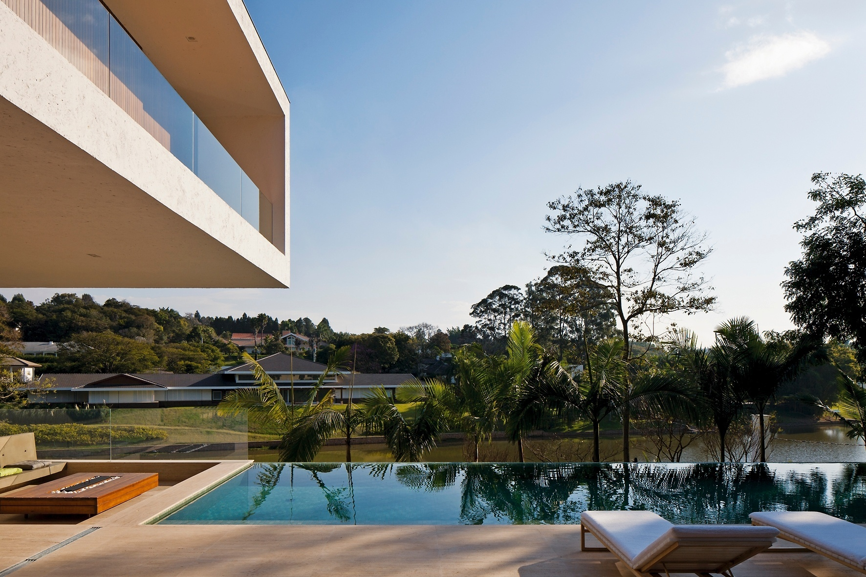 Na Casa PV, em Itu (SP), a piscina em tom esverdeado, de borda infinita, se integra ao lago e a vegetação do condomínio fechado. À esquerda é possível ver parte do andar superior, em balanço. O projeto de arquitetura é assinado por Sérgio Sampaio