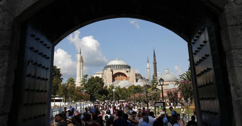 Turistas e locais passeiam pela praça Sultanahmet em Istambul, com o monumento  Hagia Sophia, da era bizantina, ao fundo