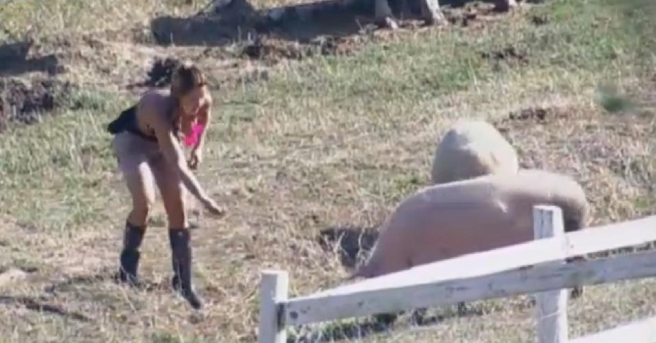 24.ago.2013 - Denise tenta chamar a atenção dos porcos na manhã deste sábado