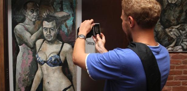 """Visitante fotografa a pintura """"Travesti"""", de Konstantin Altunin, em uma exposição no """"Museu do Poder"""", em São Petersburgo (Rússia). A obra representa o presidente Vladimir Putin e o primeiro-ministro Dimitri Medvedev vestidos de mulher - Stringer/Reuters"""