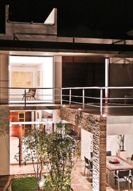 A iluminação noturna dramatiza o acabamento de pilares e viga em canjiquinha mineira, destacando a textura do material. Nos fundos da residência os ambientes sociais, de frente para a piscina, se configuram como solário, na cobertura, e churrasqueira