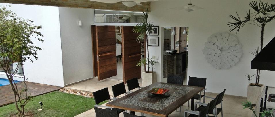 Churrasqueira (Largrill) e forno de pizza compõem a cozinha externa com espaço para a mesa de pastilhas de vidro desenvolvida pela artista Nilza Rezende. O ambiente social, de frente para a piscina, também está conectado ao solário, na cobertura, através de uma escada caracol. A Casa Pernambuco, no Guarujá (SP), tem projeto do arquiteto Flavio Castro