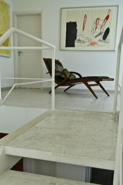 O hall dos dormitórios, no pavimento superior da Casa Pernambuco, exibe quadros da Galeria Almavera e uma chaise Maria Jovem. A escada metálica possui degraus estruturados em cimento queimado