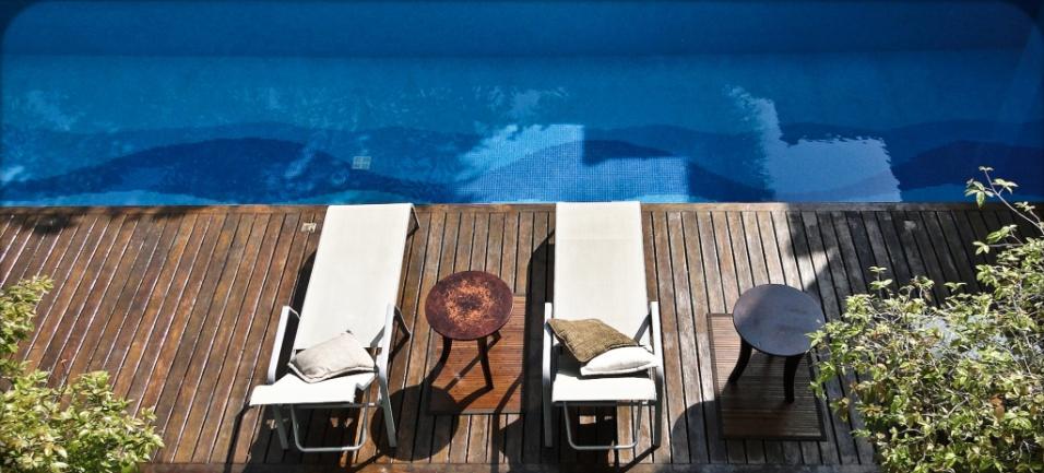 O deck da piscina na Casa Pernambuco, levemente sombreado por pitangueiras, é feito de madeira cumaru (Madesan) envernizada brilhante e o revestimento subaquático é composto por pastilhas de vidro em três tons de azul (Kolorines). O desenvolvimento e a execução artesanal da composição do desenho são assinados por Nilza Rezende. A arquitetura é de Flavio Castro