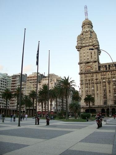 A cerimônia de recolhimento da bandeira uruguaia hasteada na Praça Independência, tendo como moldura o Palácio Salvo