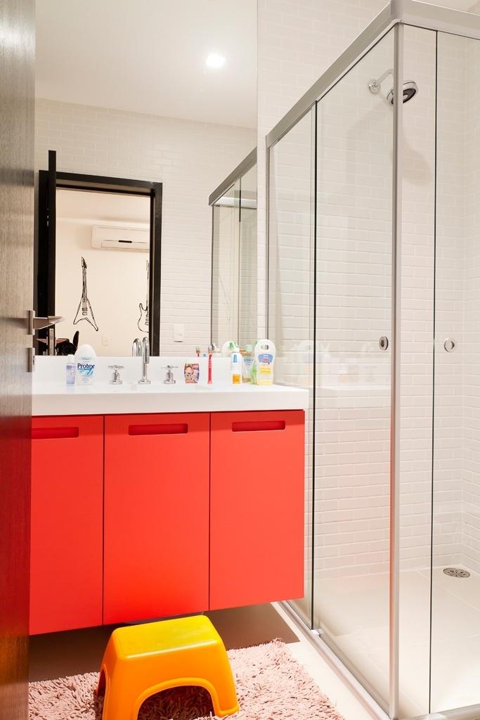 Bem ao gosto das crianças, o banheiro dos filhos recebeu colorido vibrante com o gabinete em laminado vermelho e um banquinho amarelo que deixa a bancada na altura certa para a criançada. A Casa Urbana foi projetada pela arquiteta Paula Bittar