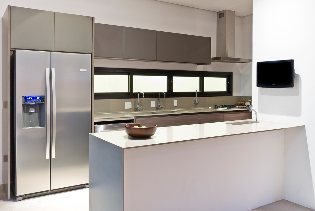 Integrada à sala de jantar, a cozinha possui design minimalista, armários altos e bancada em MDF branco e cinza, em sintonia com o aço inox dos eletrodomésticos. A Casa Urbana foi projetada pela arquiteta Paula Bittar