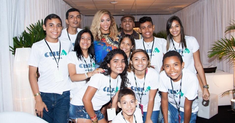 8.set.2013 - Antes de se apresentar em Fortaleza (CE), Beyoncé posa com jovens da ONG Cufa (Central Única das Favelas)