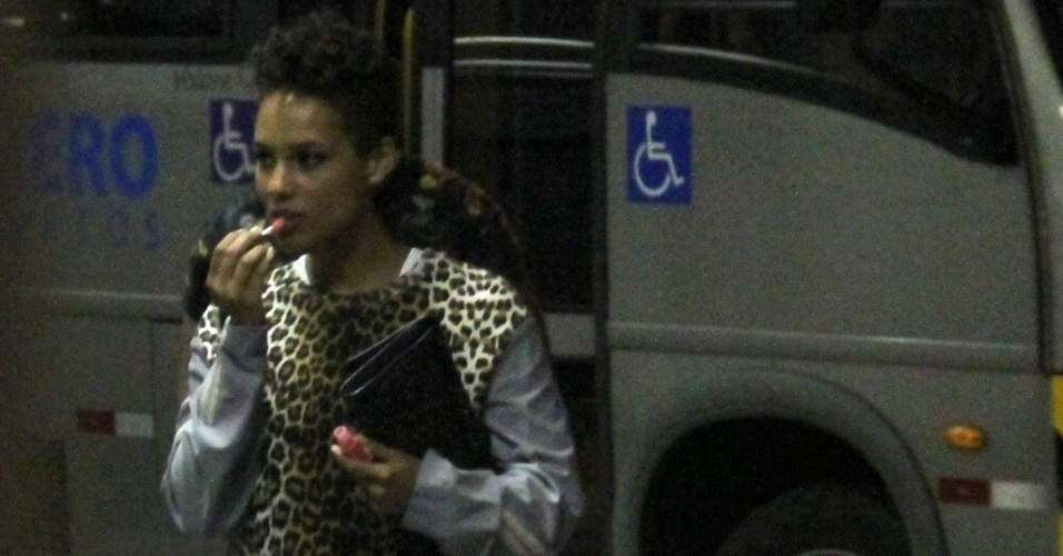9.set.2013 - A cantora Alicia Keys retoca a maquiagem ao desembarcar no aeroporto Santos Dumont, no Rio de Janeiro