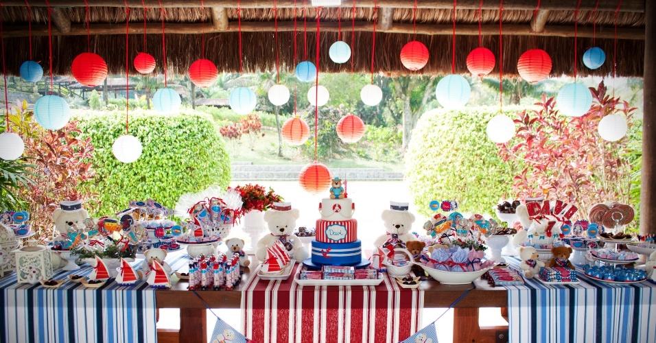 Lanternas japonesas pendentes do teto completaram o charme da mesa do bolo na festa de aniversário com o tema ursinho marinheiro