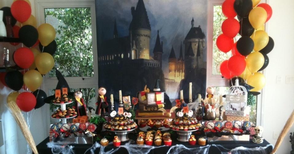 Mesa de aniversário inspirada na série de livros e filmes HarryPotter, organizada pela Studio Decor Eventos (www.studiodecoreventos.com.br). O bolo e os doces são da Sweet Carolina (www.sweetcarolina.com.br). O castelo do filme aparece no painel ao fundo e personagens enfeitam a mesa