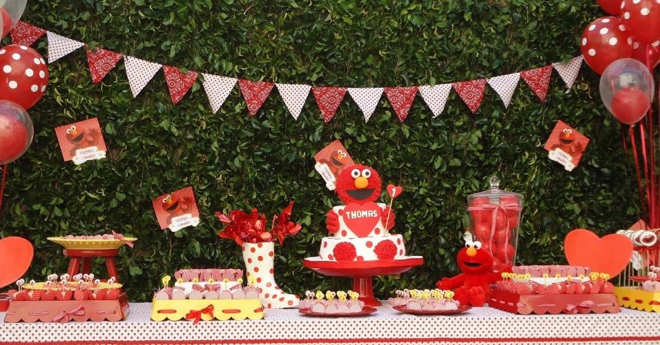 O personagem Elmo foi tema dessa festa da Moge Mug. Por causa dele, a cor vermelha prevaleceu na decoração. A mesa principal foi montada na frente de uma cerca viva que já existia na garagem da casa
