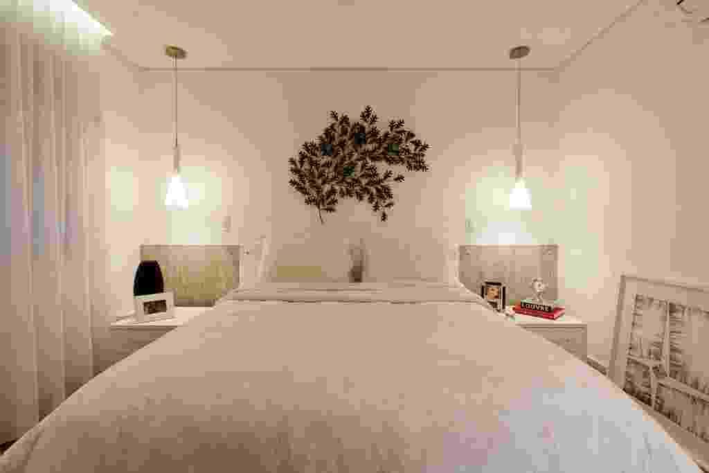 A arquiteta Mayra Lopes recorreu a tons neutros para este quarto (15 m²), cuja cabeceira em laminado remete ao desenho da madeira. A escultura de parede, sobre o leito, se destaca na composição e é ladeada por dois pendentes que substituem os abajures. A roupa de cama estampada bege clara dá o toque romântico ao dormitório - Marcelo Scandaroli/ Divulgação