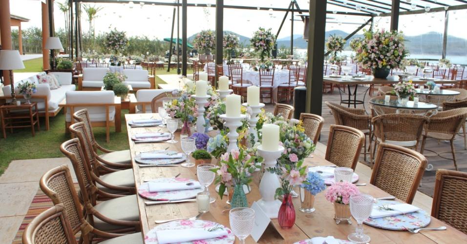 Decoração de casamento rústica, com flores variadas e mobília de madeira, feita por Fábio Borgatto & Telma Hayashi. Destaque para os suportes de prato floridos e os guardanapos de pano enfeitados por ramalhetes