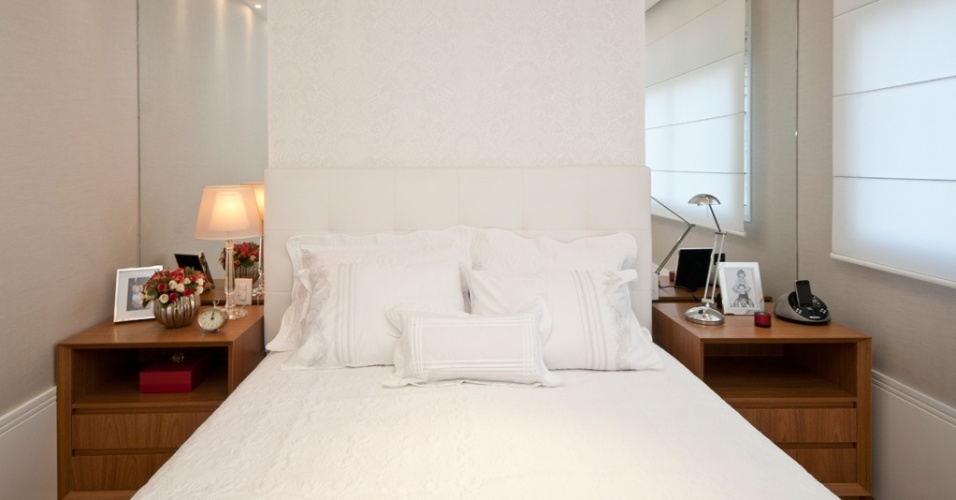 Na projeto do escritório AHGA Arquitetura o destaque fica por conta da parede atrás da cama. Nela, a cabeceira estofada se apoia sobre o papel de parede da Petit Décor decorado com arabescos em tons