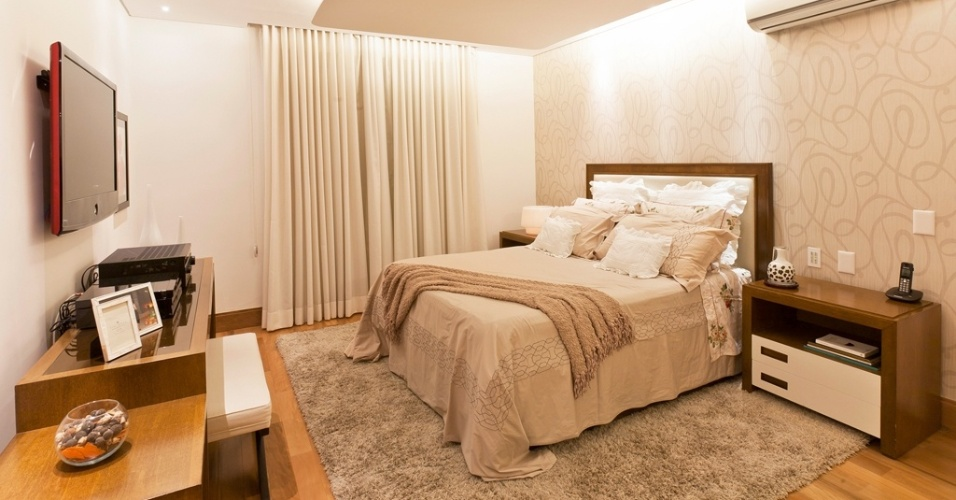Neste quarto de 24,5 m², a arquiteta Mayra Lopes recorreu ao branco, ao bege e ao amadeirado para compor a cartela de cores. Na parede atrás da cama, o papel com arabescos compõe com a cabeceira e os criados na cor uísque. No piso, o tapete felpudo em bege mais escuro leva acolhimento e protege o piso em tacão de ipê
