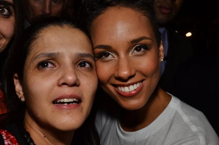 12.set.2013 - Alicia Keys (dir.) posa com fã emocionada na saída de seu show em São Paulo