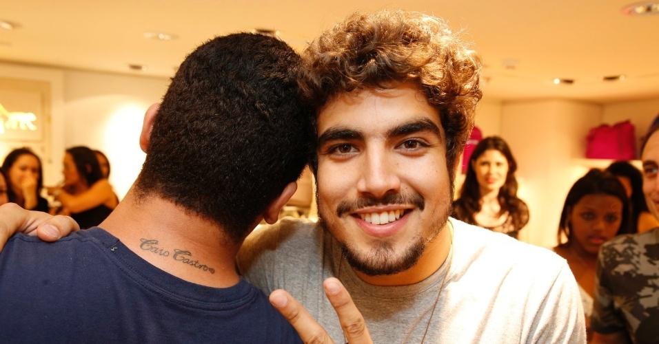 12.set.2013 - Caio Castro posa em evento em loja no Rio de Janeiro com fã que tatuou seu nome em homenagem