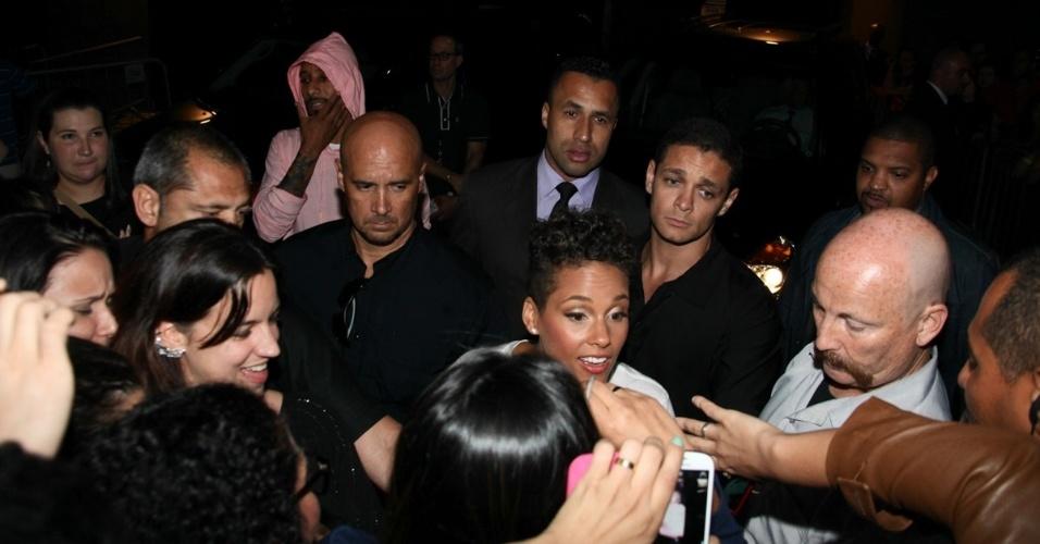 12.set.2013 - O DJ e produto Swizz Beatz (de rosa, ao fundo) observa a movimentação em volta da mulher, a cantora Alicia Keys