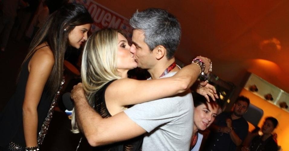 13.set.2013 - Flávia Alessandra beija o marido, Otaviano Costa. A atriz está acompanhando Otaviano, que vai trabalhar para o