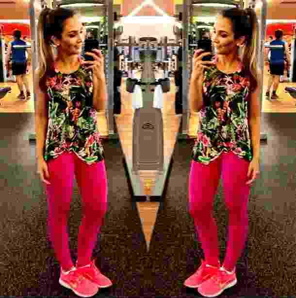 A blogueira Lalá Noleto se fotografa no espelho da academia vestindo camiseta solta com estampa floral, legging rosa combinando com o tênis e top na mesma cor - Reprodução/Instagram