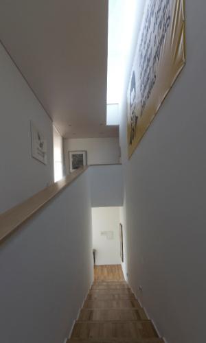 O MACh Arquitetos projetou uma escada-rampa para a circulação vertical entre pavimentos da Casa Galeria. O elemento tem formato híbrido e seus degraus são largos e com pouca inclinação, para que o percurso seja mais alongado e lento. Ao mesmo tempo em que colabora com acessibilidade, permite fruir o caminho e apreciar algumas obras de arte em exibição. O corrimão, assim como piso, é feito de peroba mica. Um rasgo no forro, para a claraboia, banha a circulação com luz natural