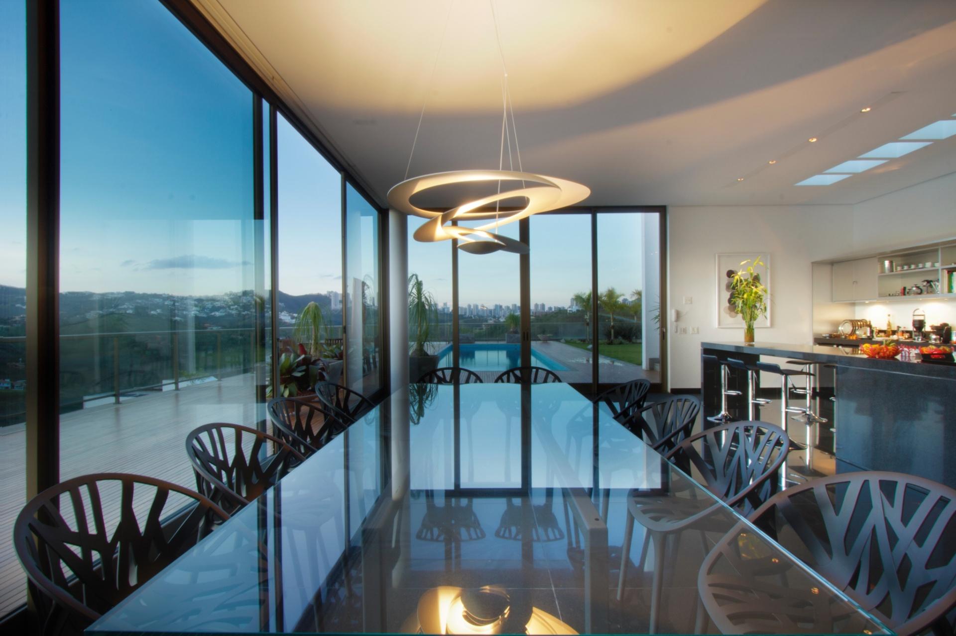 A sala de jantar integrada à cozinha é o último ambiente da longa área frontal, social e contínua da Casa Galeria. Seus fechamentos laterais são transparentes (vidro) e encaixados nas portas de correr de alumínio anodizado, que se abrem para a piscina e para a paisagem urbana de Belo Horizonte. Ao fundo, o balcão foi executado em granito preto, acompanhando o mesmo material do piso nesta área (Ergramar). A arquitetura é assinada pelo escritório MACh Arquitetos