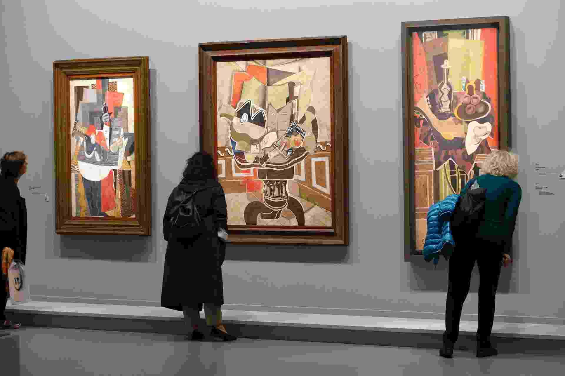 """17.set.2013 - Visitantes olham as pinturas """"Le Gueridon Rouge"""" (1939-1952), """"La Table Ronde"""" (1929) e """"Guitare et bouteille de marc sur une table"""" (1930) do artista francês Georges Braque (1882-1963) - REUTERS/Charles Platiau"""