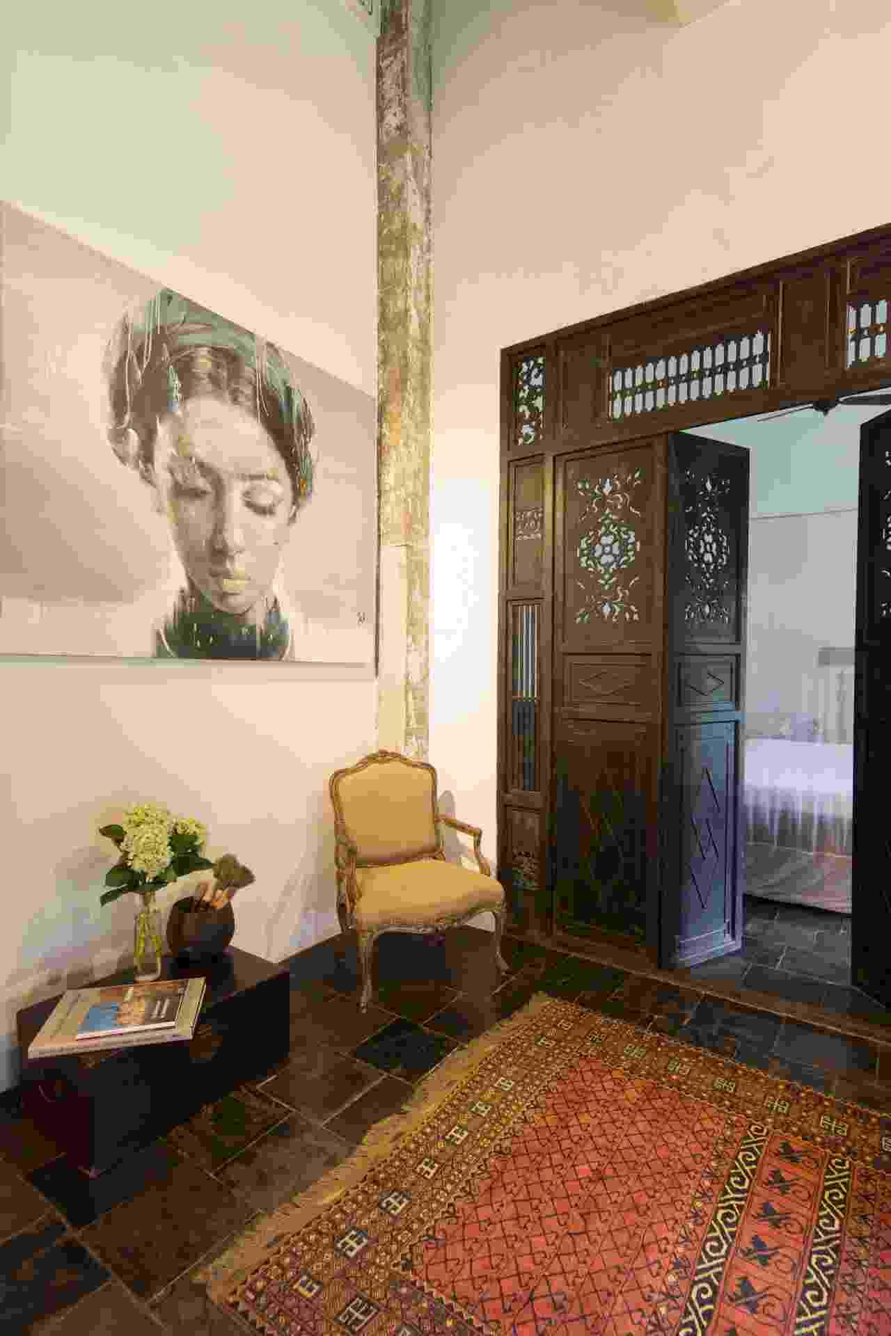 (Imagem do NYT, usar apenas no respectivo material) As portas de madeira com intrincados entalhes e recortes presta homenagem ao passado colonial francês de Ho Chi Ming, bem como as malas (à esq.), que fazem as vezes de mesa de apoio. Ainda no ambiente, a pintura de Phuong Quoc Tri (à esq.), um artista vietnamita, é combinada à cadeira estilo Luís 15 e ao tapete paquistanês - Marcel Lam/ The New York Times