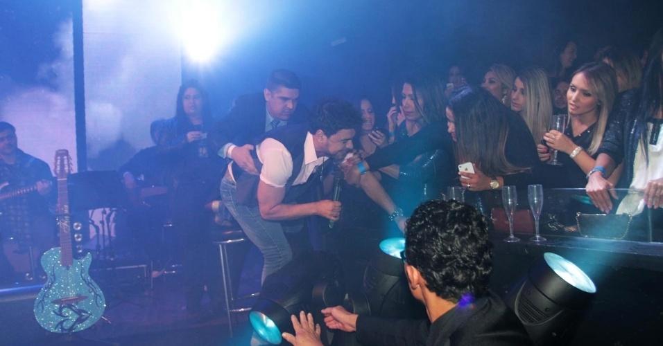 18.set.2013 - Zezé Di Camargo recebe ajuda de segurança após tropeçar e cair em canhão de luz durante show no Villa Mix, em São Paulo