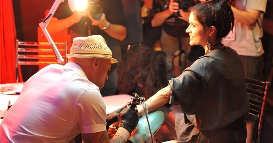 """19.set.2013 - O tatuador Ami James, conhecido pelo seriado """"Miami Ink"""", desenhou uma tatuagem em Roberta Medina durante o evento"""