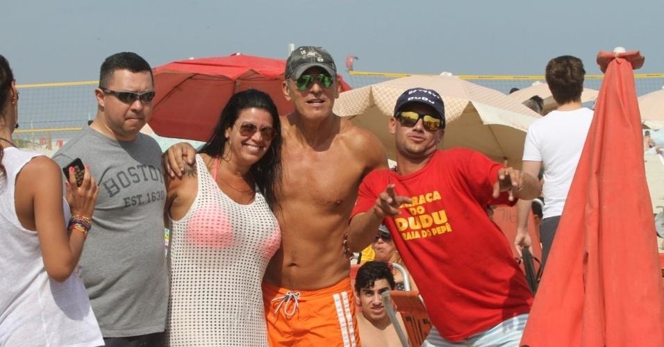 20.set.2013 - Bruce Springsteen tira foto com fãs na praia da Barra, na zona oeste do Rio. O músico é o último a se apresentar no Palco Mundo neste sábado (21)