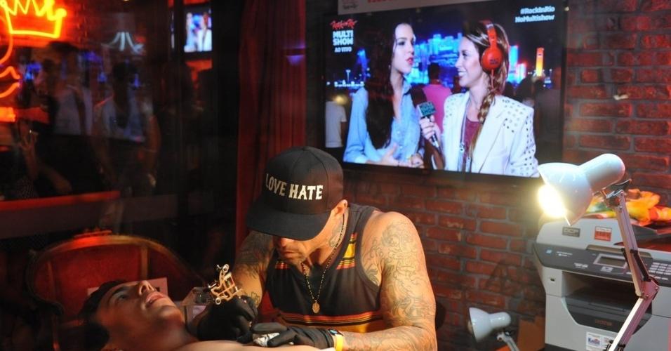 20.set.2013 - Durante a sessão de tatuagem, Mariana Rios, ex-namorada de Di, aparece no telão concedendo uma entrevista ao Multishow