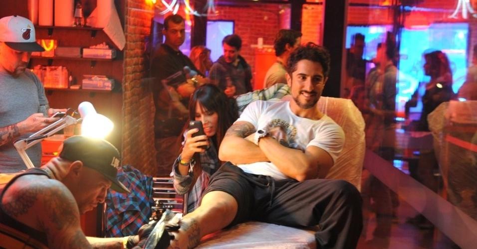 20.set.2013 - Observado pela mulher, Suzana Gullo, Marcos Mion faz uma tatuagem com Ami James, durante o Rock in Rio
