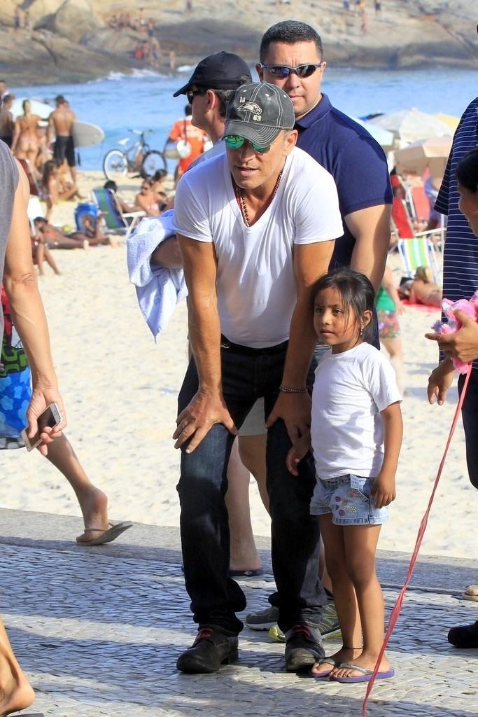 21.set.2013 - Bruce Springsteen tira foto com menina no calçadão do Arpoador. O cantor é uma das atrações deste sábado (21) do Rock in Rio